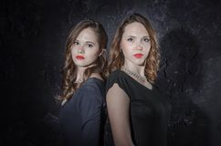 Duas namoradas consideráveis que estão junto de volta à parte traseira olhando a câmera Estúdio disparado no estilo noir Foto de Stock