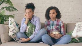 Duas namoradas encaracolado da raça misturada que sentam-se no programa televisivo nervoso do sofá e do relógio e comem a pipoca  vídeos de arquivo