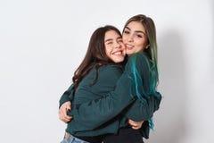 Duas namoradas felizes engraçadas das mulheres abraçam no fundo branco a amizade das mulheres, irmãs, juventude imagens de stock royalty free