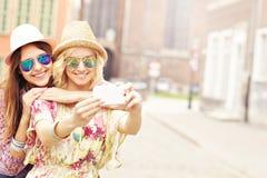 Duas namoradas felizes que tomam o selfie Imagens de Stock Royalty Free