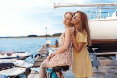 Duas namoradas que apreciam o por do sol da noite no porto Imagens de Stock