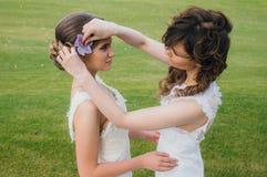 Duas noivas bonitas que corrigem o cabelo no campo verde Foto de Stock