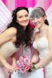 Duas noivas que desgastam os vestidos brancos prendem o ramalhete fotos de stock royalty free