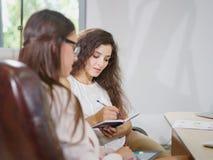 Duas novas, mulheres de negócio bonitas no escritório fotografia de stock royalty free
