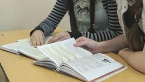 Duas páginas da aleta das meninas do livro de texto na lição video estoque