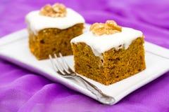 Duas partes de bolo de cenoura caseiro com laranja, entusiasmo, noz e gelado, no fundo lilás Foco seletivo Fotografia de Stock