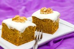 Duas partes de bolo de cenoura caseiro com laranja, entusiasmo, noz e gelado, no fundo lilás Foco seletivo Fotos de Stock Royalty Free