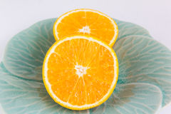 Duas partes de meias laranjas frescas na placa verde clássica Fotos de Stock Royalty Free