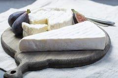 Duas partes de queijos macios franceses brie e camembert com molde branco e odor forte, serviram com os figos maduros frescos imagem de stock royalty free