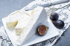Duas partes de queijos macios franceses brie e camembert com molde branco e odor forte, serviram com os figos maduros frescos fotos de stock