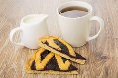 Duas partes de torta da uva-do-monte, de jarro de leite e de chá Imagens de Stock Royalty Free