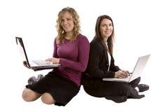 Duas partes traseiras das mulheres junto em computadores Fotografia de Stock Royalty Free
