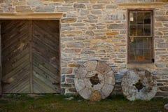 Duas pedras do moinho contra a construção Imagem de Stock Royalty Free