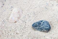 Duas pedras, luz e obscuridade, colocando separadamente na areia foto de stock royalty free