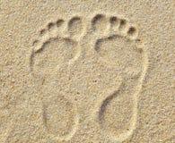Duas pegadas na areia na praia Fotografia de Stock Royalty Free