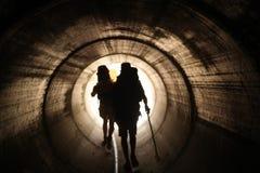 Duas pessoas andam à luz na extremidade do túnel Imagens de Stock Royalty Free