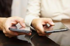 Duas pessoas comparam telefones celulares espertos Fotografia de Stock Royalty Free