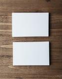 Duas pilhas de cartões brancos vazios no vertical de madeira do fundo Foto de Stock