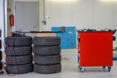 Duas pilhas de pneus de carro e de um trole da ferramenta imagem de stock royalty free