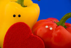 Duas pimentas com olhos e coração imagem de stock