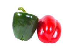 Duas pimentas - verdes e vermelho em um fundo branco Fotografia de Stock Royalty Free