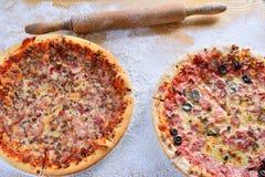 Duas pizzas deliciosas na tabela de madeira dispersaram com farinha Imagens de Stock
