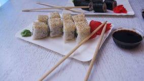 Duas placas do sushi Rolls em um restaurante japonês em uma tabela de madeira à moda branca Tiro da zorra vídeos de arquivo