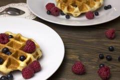 Duas placas dos waffles e das framboesas das bagas Mirtilos fotografia de stock royalty free