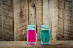 Duas poções de vidro mágicas com líquido azul e vermelho na tabela de madeira Fotos de Stock