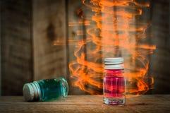 Duas poções de vidro mágicas com líquido azul e vermelho na tabela de madeira com efeito mágico amarelo Fotografia de Stock