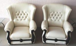 Duas poltronas do couro branco imagens de stock