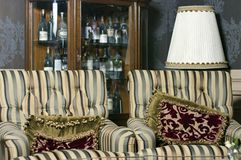 Duas poltronas do vintage com as garrafas do vinho velho no armário Imagens de Stock