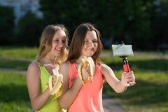 Duas raparigas Bloggers novos e bloggers Sorriso felizmente Guarda o smartphone em suas mãos, escreve o vídeo no Fotos de Stock Royalty Free