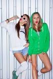 Duas raparigas bonitas com os pirulitos vermelhos perto da parede Foto de Stock