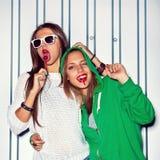 Duas raparigas bonitas com os pirulitos vermelhos perto da parede Imagem de Stock
