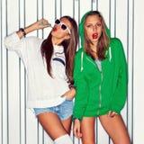 Duas raparigas bonitas com os pirulitos vermelhos perto da parede Fotografia de Stock