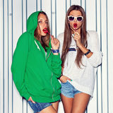 Duas raparigas bonitas com os pirulitos vermelhos perto da parede Foto de Stock Royalty Free