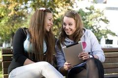Duas raparigas com PC da tabuleta imagem de stock royalty free