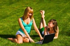 Duas raparigas na grama com caderno Fotos de Stock Royalty Free