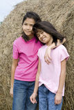 Duas raparigas que estão pelo haybale Foto de Stock Royalty Free