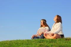Duas raparigas sentam-se e meditate na grama verde foto de stock royalty free