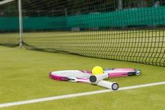 Duas raquetes de tênis com uma bola de tênis que encontra-se perto da rede em um verde Fotografia de Stock