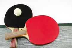 Duas raquetes de tênis de mesa e uma rede isolada Imagem de Stock