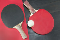 Duas raquetes de tênis de mesa em fundos vermelhos e pretos Imagem de Stock Royalty Free