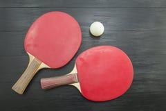Duas raquetes de tênis de mesa vermelhas no fundo escuro Fotografia de Stock Royalty Free