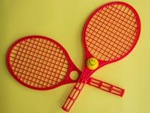 Duas raquetes de tênis plásticas pequenas vermelhas no papel amarelo fotos de stock