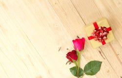 Duas rosas e caixas de presente de florescência em um assoalho de madeira Imagens de Stock Royalty Free
