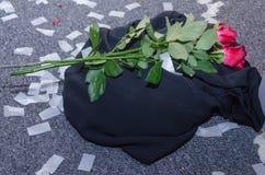 Duas rosas vermelhas em um lenço preto no assoalho e nos confetes brancos Imagem de Stock