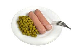 Duas salsichas fervidas quentes com as ervilhas verdes enlatadas em uma placa branca são servidas para o jantar Imagem de Stock