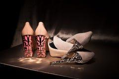 Duas sapatas colocadas saltos do encanto dos pares elevação dourada Fotos de Stock Royalty Free
